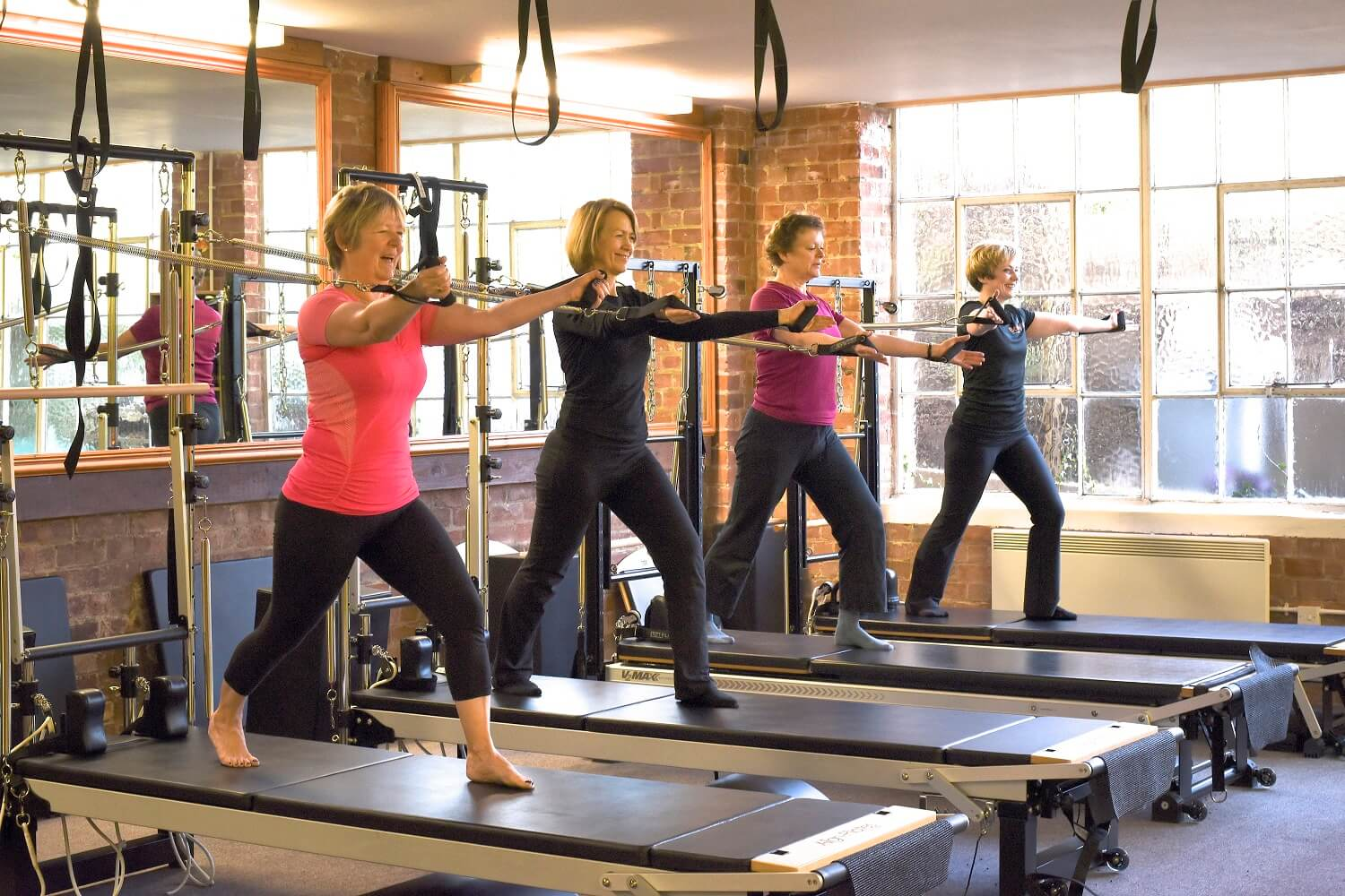 ladies standing on reformer beds